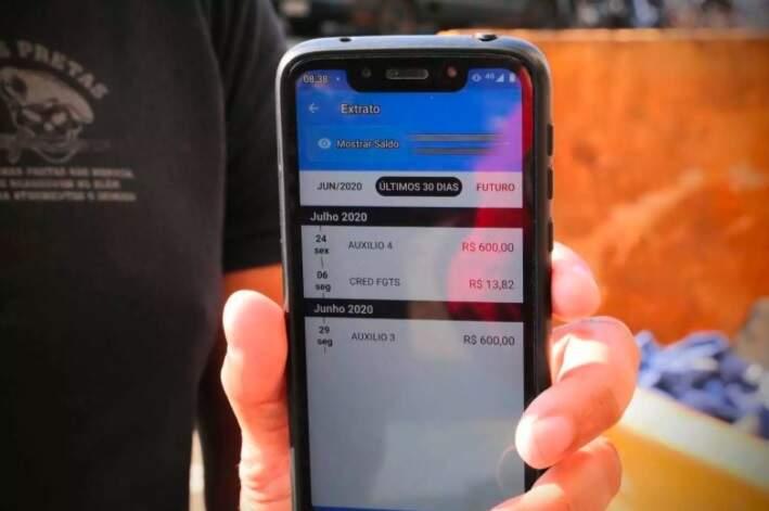 Beneficiário confere saldo do auxílio no celular (Foto: Kísie Ainoã/Arquivo)
