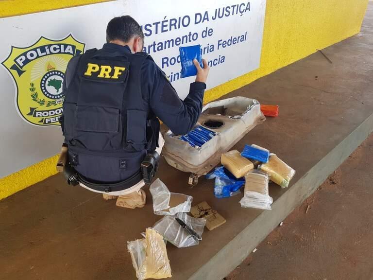 Policial retirando os tabletes da droga de dentro do tanque do veículo. (Foto: PRF)