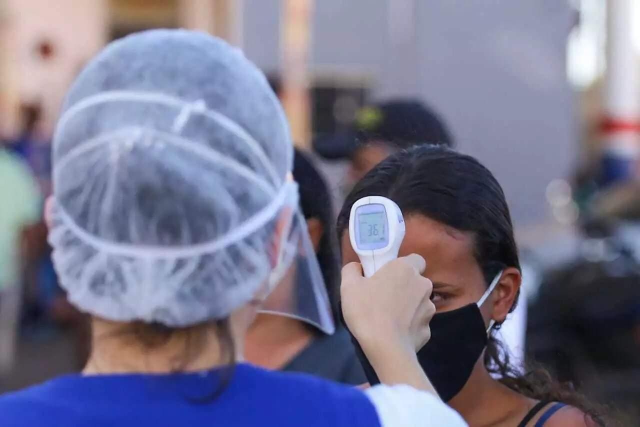 Profissional de saúde afere temperatura de pessoa em Campo Grande (Foto: Arquivo)