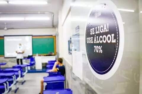 Placa alerta para a necessidade de uso de álcool 70% pelos alunos na precaução à covid-19. (Foto: Arquivo/Campo Grande News)