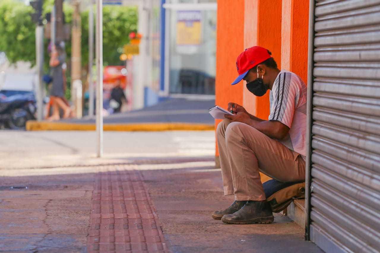 Rapaz faz anotações no Centro da Capital e mesmo sem ninguém por perto mantém a máscara no rosto (Foto: Marcos Maluf/Arquivo)