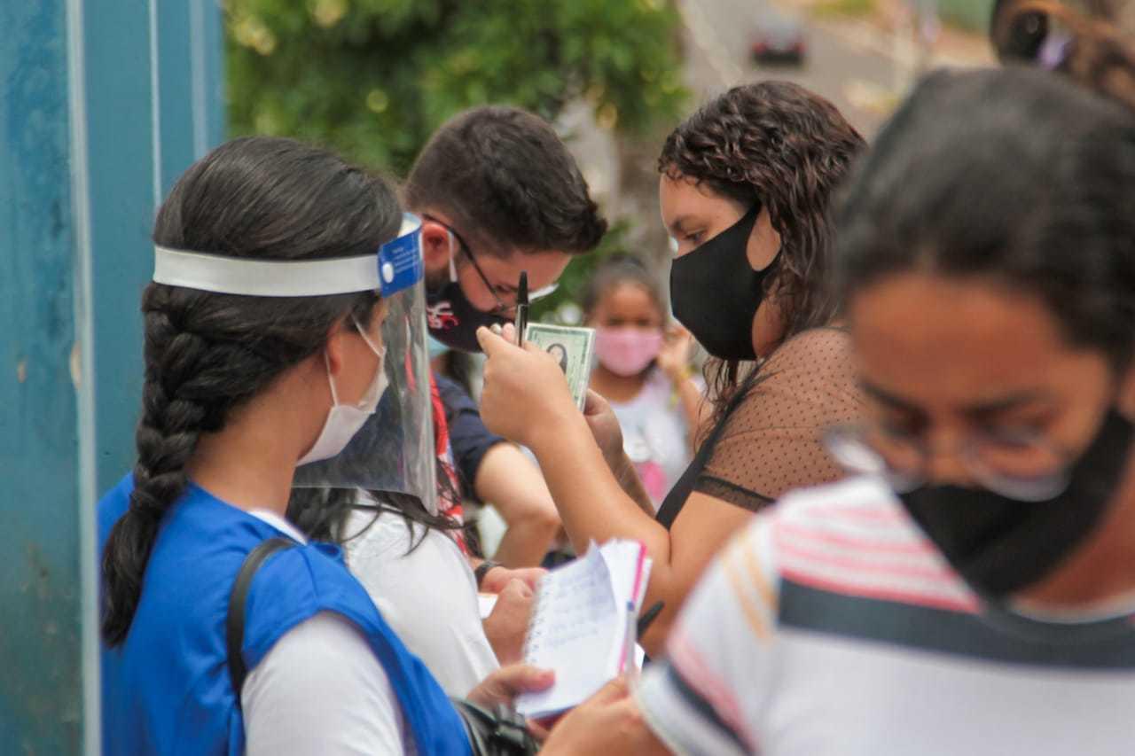 Protegidos contra a covid,19, candidatos aguardam entrada para o Enem. (Foto: Marcos Maluf)