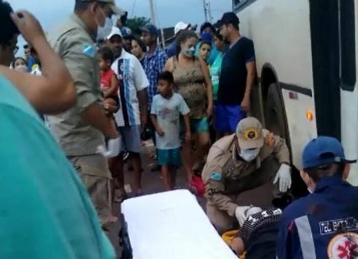 Momento em que bombeiro e agente do Samu retiram mulher debaixo do coletivo. (Foto: Tá Na Mídia Naviraí)