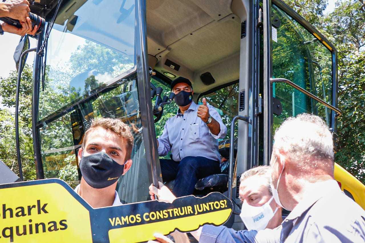 Governador Reinaldo Azambuja sobe em máquina agrícola durante entrega do equipmento (Foto: Henrique Kawaminami)