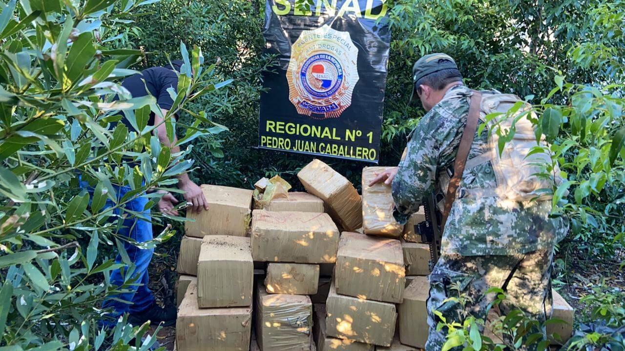 Agentes da Senad empilham fardos de maconha encontrados na fronteira (Foto: Divulgação)