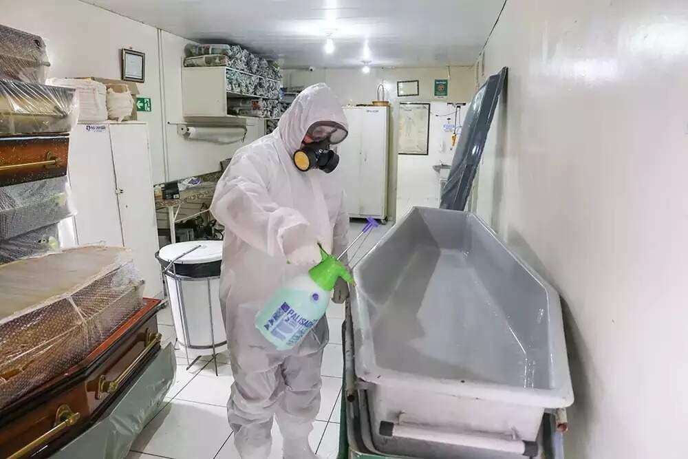 Funcionário de funerária higienizando urna para transporte de corpos em Campo Grande (Foto: Paulo Francis/Arquivo)