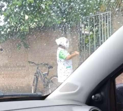 Com sacola na cabeça, nem chuva impede auxiliar de enfermagem de vacinar