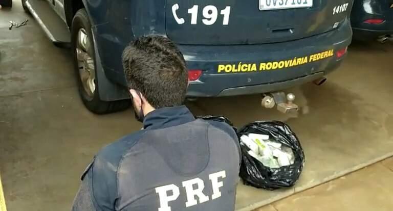 Policial ao lado dos tabletes da droga apreendida. (Foto: PRF)