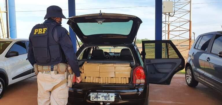 Policial diante dos tabletes de maconha encontrados no porta-malas do veículo. (Foto: PRF)