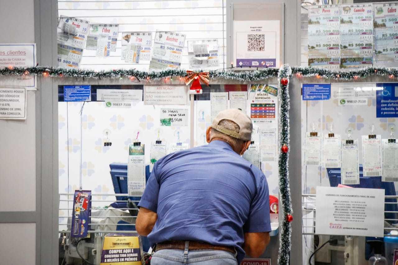 Cliente sendo atendido em lotérica, local onde os beneficiados do auxílio podem receber os pagamentos. (Foto: Henrique Kawaminami)