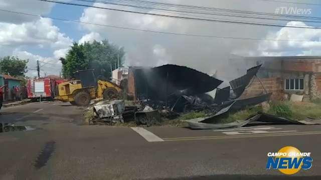 Retroescavadeira faz retirada de materiais em depósito atingido por incêndio